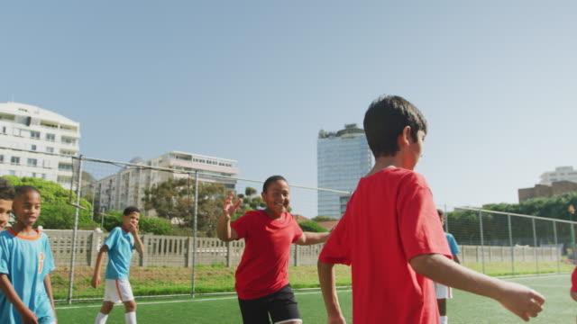 fußballkinder spielen an einem sonnigen tag - geköpft stock-videos und b-roll-filmmaterial