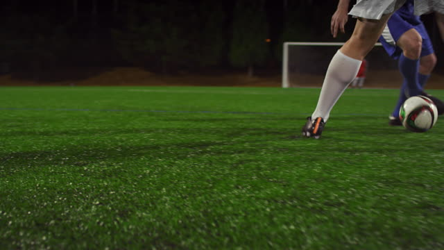 A soccer player dribbles down the field during a game at night video