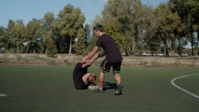fotbollsspelare hjälpa lagkamrat att gå upp efter foul - assistans bildbanksvideor och videomaterial från bakom kulisserna