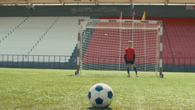Soccer player kicking ball in children match Small goalie waiting on his post while opposite player taking a run and kicking ball, but shooting wide goal post stock videos & royalty-free footage