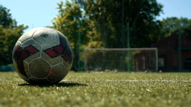 Soccer player kicking ball on field, close up