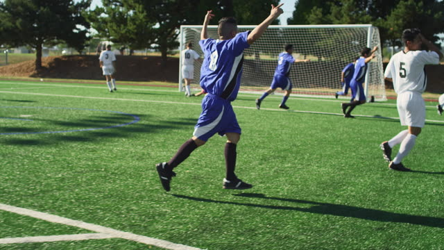A soccer player makes a goal and the team hugs and celebrates A soccer player makes a goal and the team hugs and celebrates scoring a goal stock videos & royalty-free footage