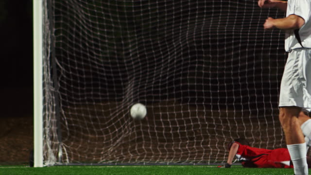 A soccer player making a penalty kick past the goalkeeper video