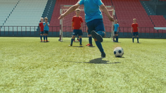 Soccer player making goal on professional kid match Little soccer player kicking ball through wall and making goal on stadium goal post stock videos & royalty-free footage