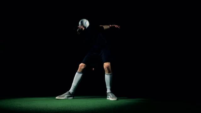 stockvideo's en b-roll-footage met voetbalspeler spelen met een voetbal bal maken trucs. slow-motion. - sportcompetitie