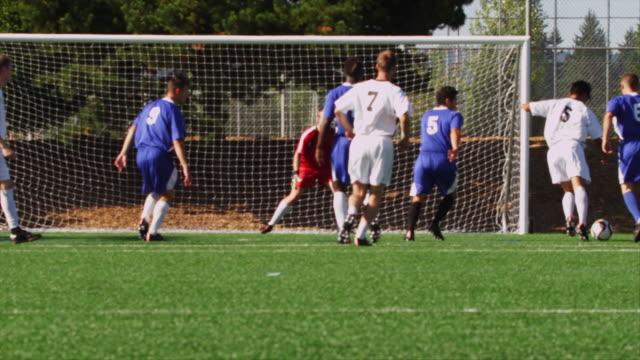 vídeos y material grabado en eventos de stock de un jugador de fútbol de los puntajes de un objetivo y celebra con sus compañeros de equipo - meta