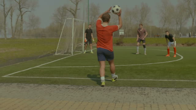 Soccer player throwing the ball in onto the pitch