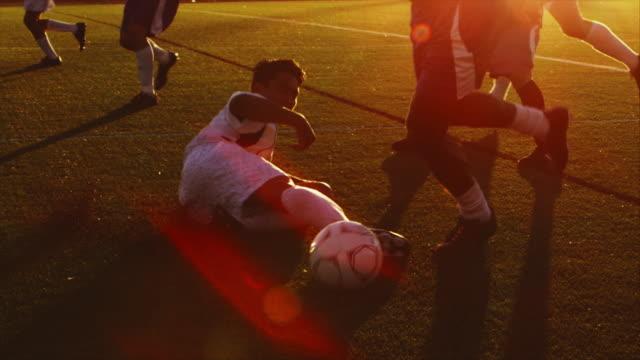 vídeos de stock, filmes e b-roll de um jogador de futebol tenta slide atacar seu adversário ao pôr-do-sol - medicina esportiva