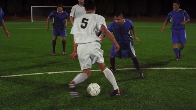 Soccer players pass the ball down the field at night video
