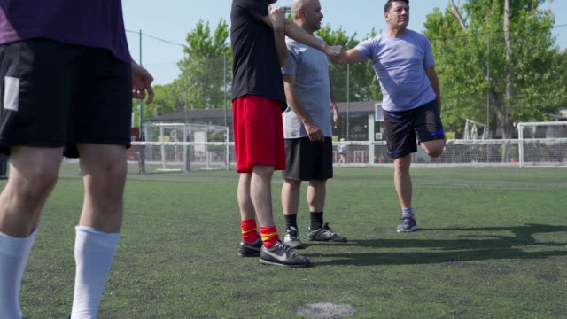 Soccer teammates doing pregame routine Group of friends doing pregame routine, stretching on soccer field pre game stock videos & royalty-free footage