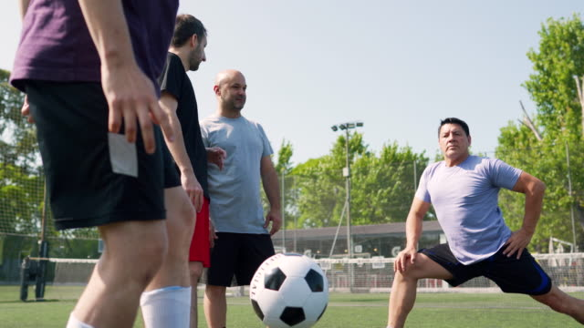 Soccer teammates doing pregame warm up routine Group of friends doing pregame warm up routine, stretching on soccer field pre game stock videos & royalty-free footage