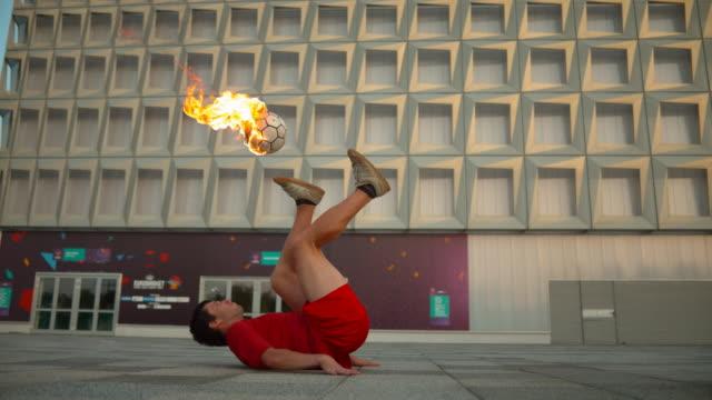 soccer tricks with a burning soccer ball, ultra slow motion - трюк стоковые видео и кадры b-roll