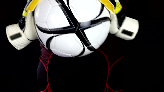 Soccer/football goalkeeper putting his gloves on a black background video