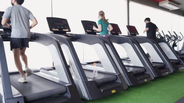 Social Distancing - Running on treadmill in gym Social Distancing - Running on treadmill in gym health club stock videos & royalty-free footage