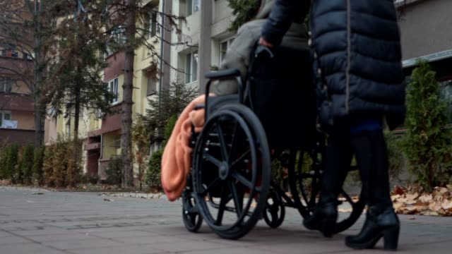 Social worker transporting an elderly woman in a wheelchair Social worker transporting an elderly woman in a wheelchair on a cold autumn day pushing wheelchair stock videos & royalty-free footage