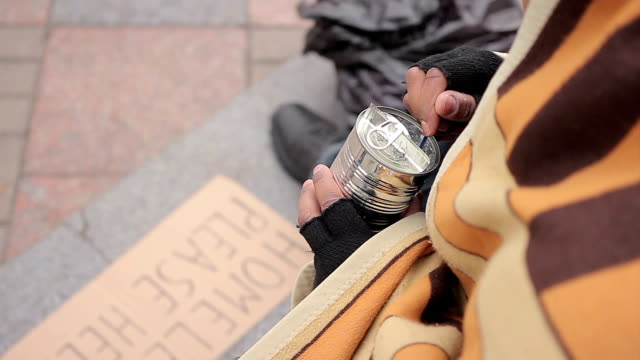 Socially vulnerable homeless person eating canned food in street, poverty issue video