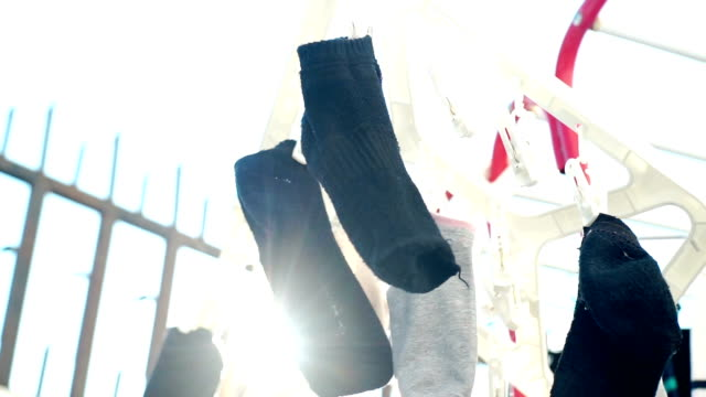 socks hanging on the clip for dry clothes on daytime. - calzino video stock e b–roll