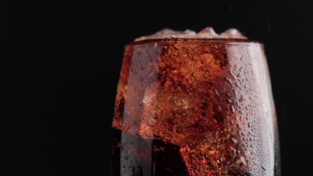 vídeos de stock e filmes b-roll de soda fizzy cold drink in a glass with ice cubes close-up on a black background - bebida fresca