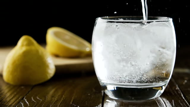 Soda water with ice cubes and lemon in the drink glass. Pouring transparent soda water into a glass. Soda water with ice cubes and lemon in the drink glass. tonic water stock videos & royalty-free footage