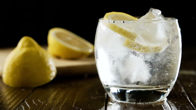 Soda water with ice cubes and lemon in the drink glass. Lemon fall into a glass with ice, slow motion. Cocktail concept. Soda water with ice cubes and lemon in the drink glass. tonic water stock videos & royalty-free footage