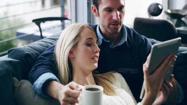 Sofa entertainment sorted thanks to smart technology 4K video footage of a loving young couple using a digital tablet together on the sofa at home surfing the net stock videos & royalty-free footage