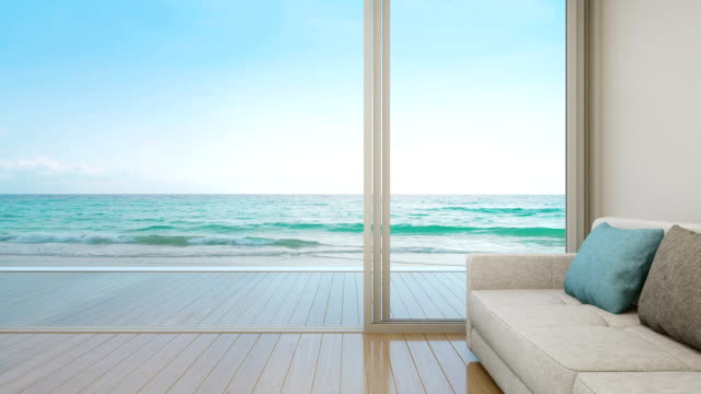 Sofa on wooden floor near glass door with ocean and sky background at luxury apartment, Lounge in sea view living room of modern beach house or hotel 3D rendering of interior with terrace summer background stock videos & royalty-free footage