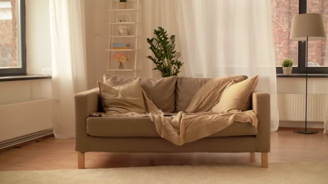 sofa with cushions at cozy home living room comfort, furniture and interior concept - sofa with cushions at cozy home living room blanket stock videos & royalty-free footage