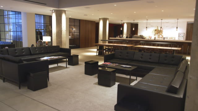 sofas and coffee tables in empty business lounge interior - hotel checkin video stock e b–roll