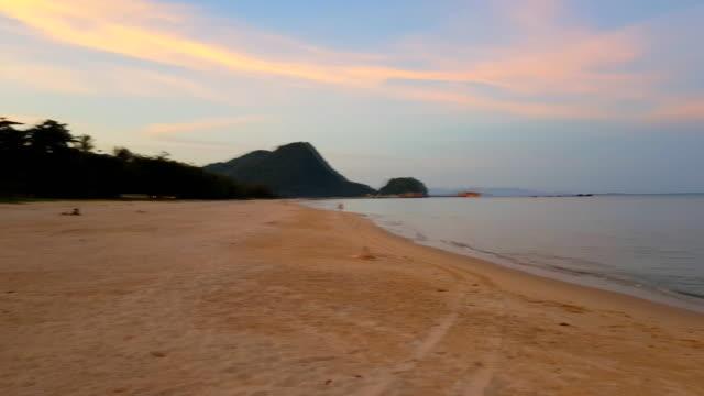 stockvideo's en b-roll-footage met zachte golf van blue ocean op sandy beach met oranje avondrood - grace bay