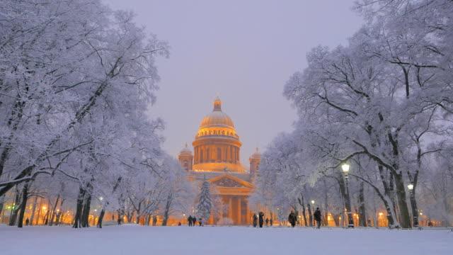 soft winter evening view at snowy park and isaakievskiy sobor, saint petersburg - san pietroburgo russia video stock e b–roll