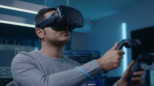 Software Delevoper Wearing Virtual Reality Headset Gesturing with Controllers to Develop and Program VR Gaming and Applications. In the Background Technology Developing Studio with Computers and Monitors