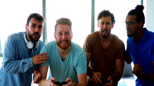 yazılım geliştiricileri bir mola video oyunları oynuyor. - orta yetişkin stok videoları ve detay görüntü çekimi