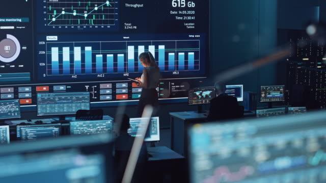 programvaruingenjörer som arbetar i ett rum med en stor skärm i ett modernt övervakningskontor med liveanalysflöde med diagram. övervakning room big data forskare och chefer sitter framför datorer. - server room bildbanksvideor och videomaterial från bakom kulisserna