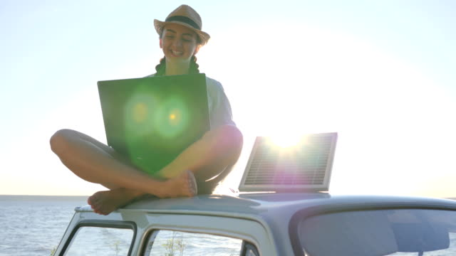 solar energy, female sitting on vintage car with notebook and battery on background sky in sunlight, girl sits on roof blue video
