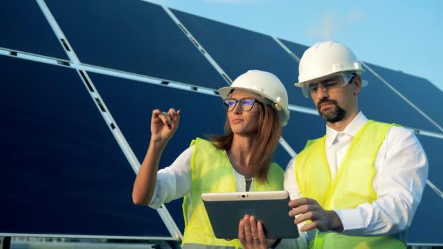 ingegneri solari che parlano vicino ai pannelli solari. concetto di energia verde. - sostenibilità video stock e b–roll