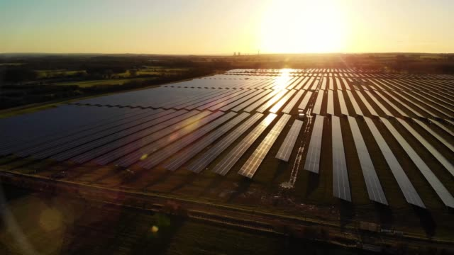 Solar farm at dawn Sunrise over a modern electric solar farm with the sun glistening over the panels as the camera pans over them from the air power stock videos & royalty-free footage