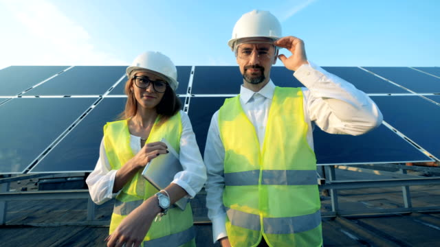 vídeos de stock e filmes b-roll de solar installation and two inspectors standing in front of it and smiling looking into camera. - solar panel