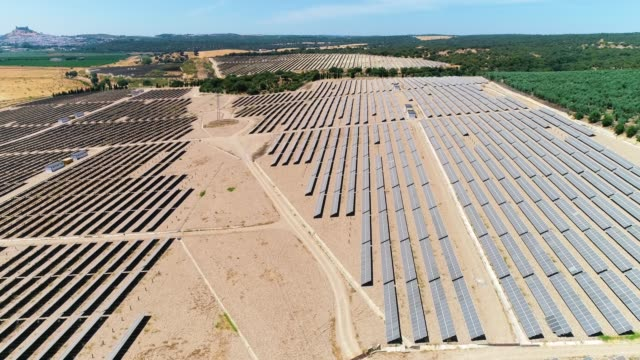Solar panels farm in Spain. There is the reflection of the sun in the the panels which produce renewable energy, solar energy. - aerial view wih a drone - environment and renewable energy concept