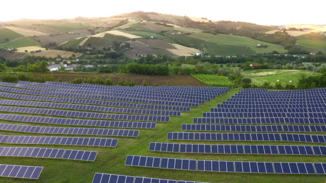 Solar panels fields on the green hills - video