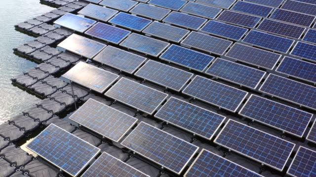 vídeos de stock e filmes b-roll de solar panels in aerial view, rows array of polycrystalline silicon solar cells or photovoltaics in solar power plant floating on the water in lake. - solar panel