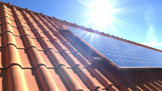 vídeos de stock e filmes b-roll de solar panels modules on roof with sun reflecting - equipamento solar
