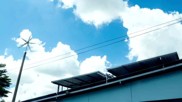 Solar panels on a roof and Wind Turbine with Blue Sky and Cloud Background video