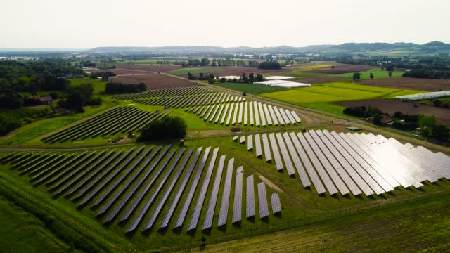 フランスの太陽光の下で太陽光パネルのフィールド - 航空写真 - 環境保全、気候変動、太陽光、草、光の反射、保護、電気、持続可能なエネルギー、緑 - オルタナティブカルチャー点の映像素材/bロール