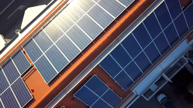 vídeos de stock e filmes b-roll de solar power panels on top of residential building roof for producing of green ecological electricity. - solar panel
