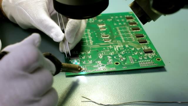 soldering smd resistors on pcb - pinze attrezzo manuale video stock e b–roll