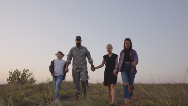 soldier and his family walking on a meadow - military lifestyle stock videos & royalty-free footage