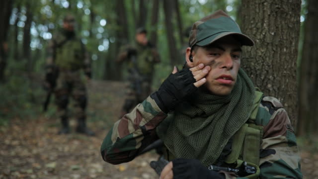 Soldier applying face paint Soldiers in camouflaged clothing, one soldier is putting black paint on face, deep in wilderness. camouflage clothing stock videos & royalty-free footage
