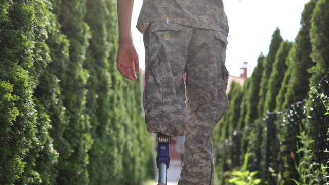 Soldier Coming Home From Serving Military With Amputee Leg Young Amputee Soldier Coming Home  From Serving Military; With leg In Orthopedic Prosthesis camouflage clothing stock videos & royalty-free footage