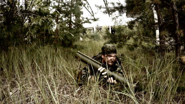 Soldier crawling in the grass, and then prepares RPG aiming video
