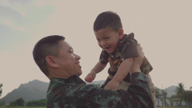 soldier father holding and playing his son in a park - military lifestyle stock videos & royalty-free footage